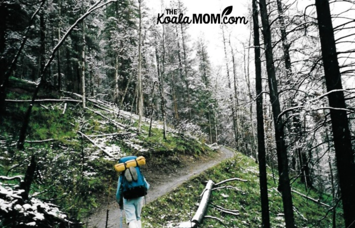 Woman hiking the Lake Minnewanka trail with snow falling.