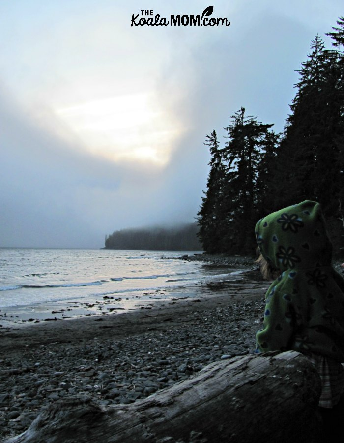 Toddler sitting on a log on China Beach, watching the sunset over the waves.