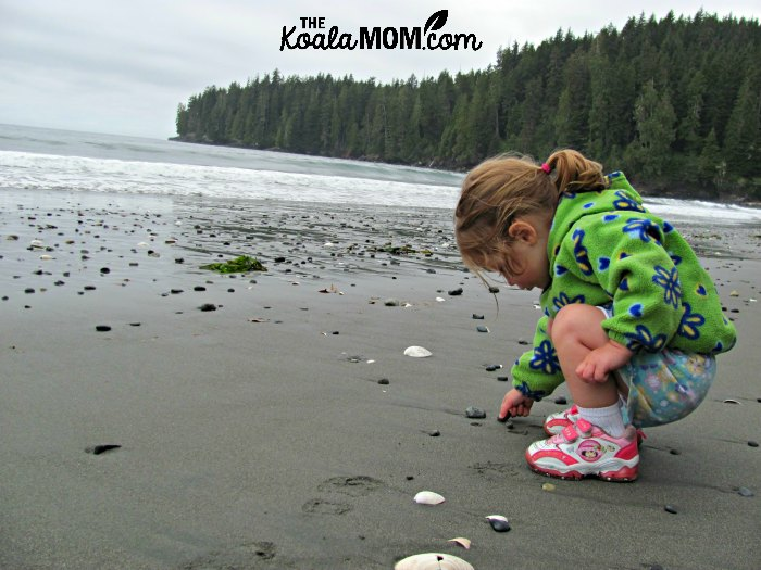 Toddler in bright clothes playing with rocks on a beach.