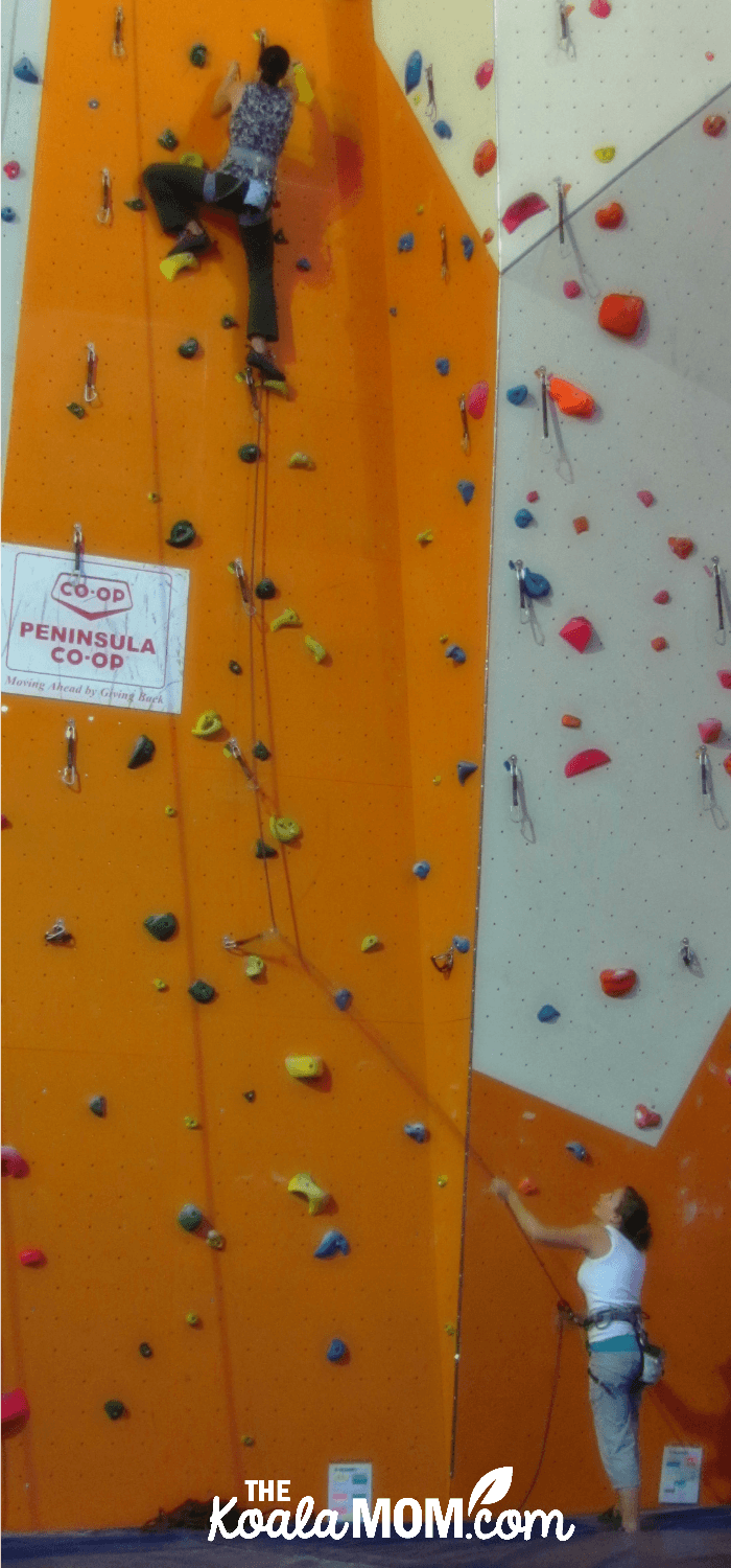 My cousin belays me on a rock climbing wall.