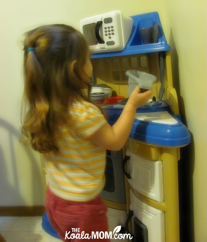 Three-year-old playing at her toy kitchen