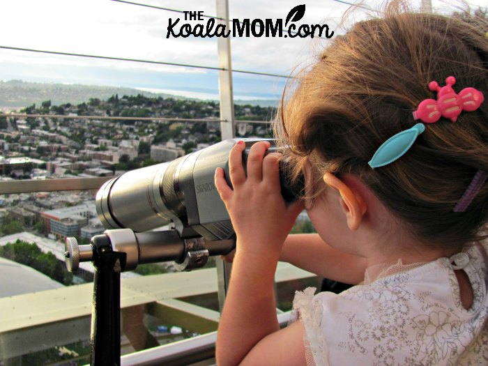 Toddler using a telescope to view Seattle from the Space Needle