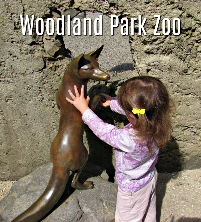Toddler petting a statue at the Woodland Park Zoo.