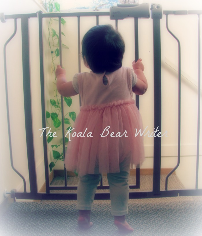 Baby girl standing at a baby safety gate