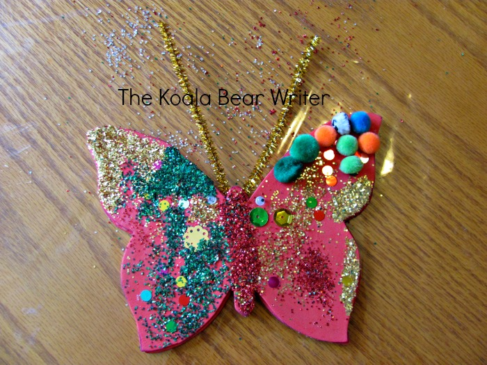 Foam butterfly covered with glitter and pompoms