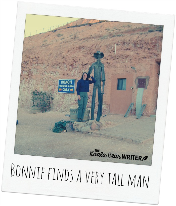 Bonnie with a tall metal man in Coober Pedy, Australia