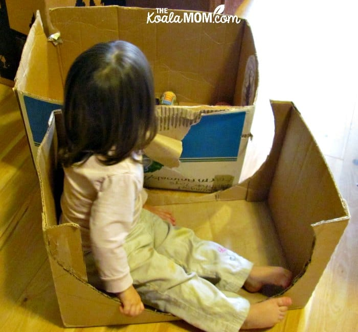 Toddler sitting in a simple cardboard box car.