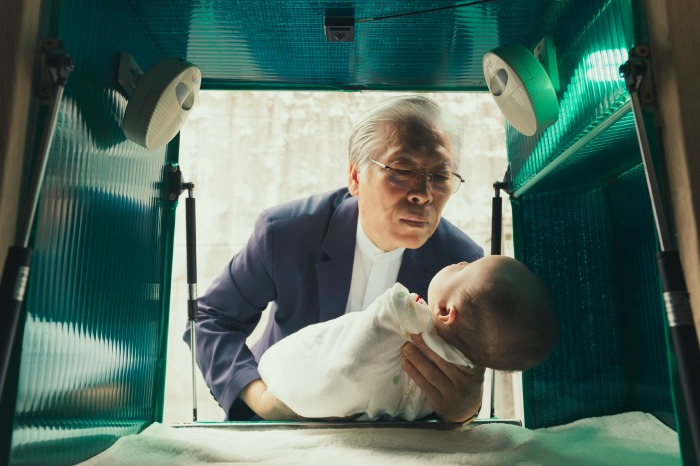 Pastor Lee Jong-rak lifts an abandoned baby from the dropbox outside his home in South Korea.