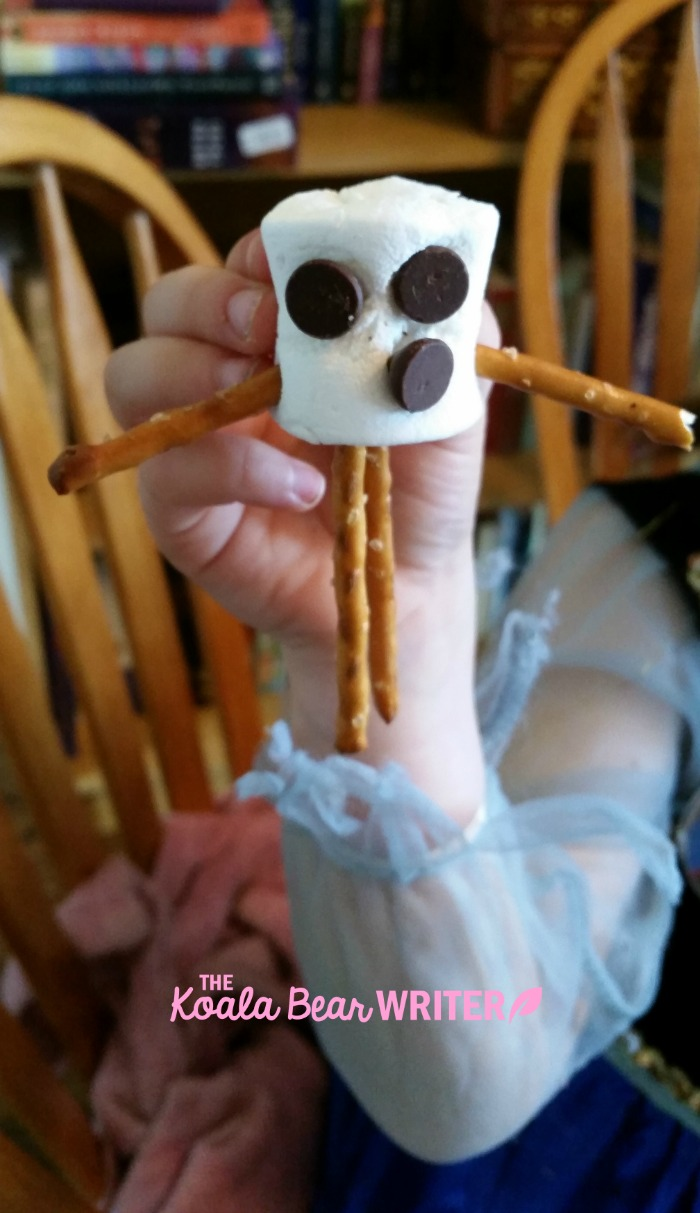 An Olaf snowman made from a marshmallow, chocolate chips and pretzels.