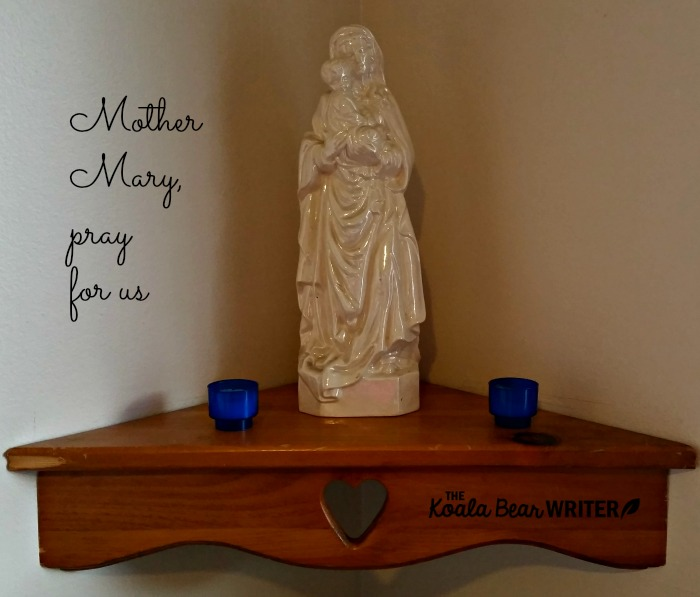 A Mary shrine with a statue and two candles.