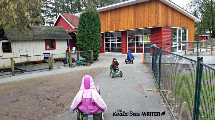 Three girls riding mini tractors at Maplewood Farm in Vancouver, BC