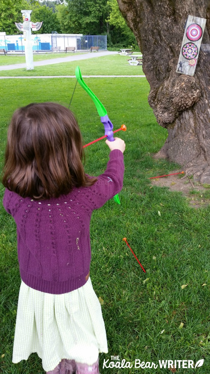 Lily shooting a bow and arrow like Merida in Disney's Brave movie