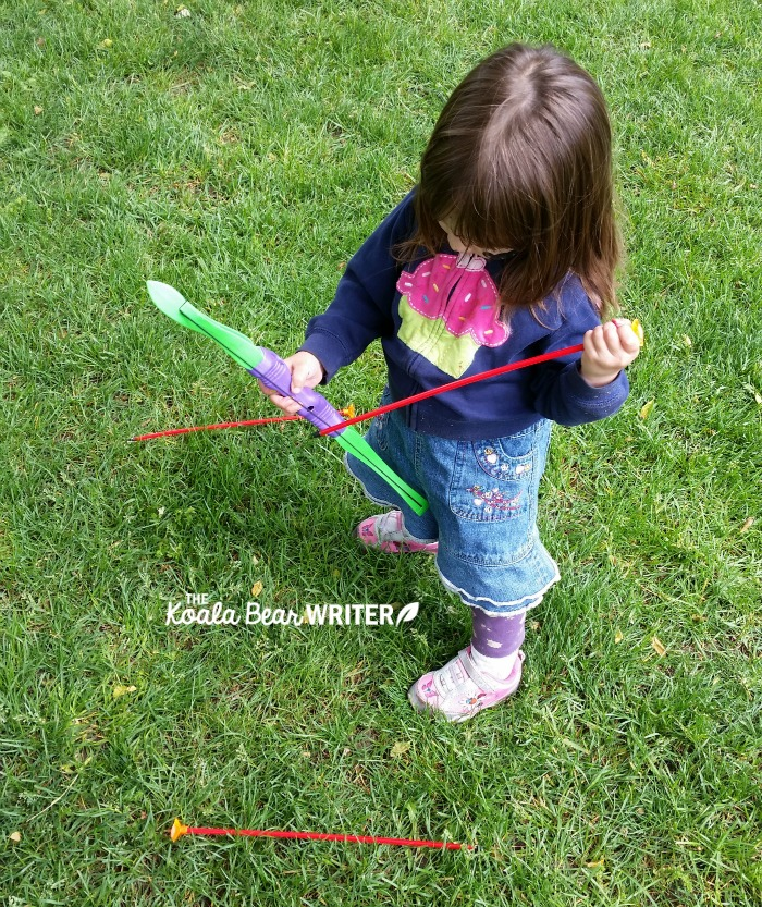 Toddler trying to figure out a toy bow and arrow.