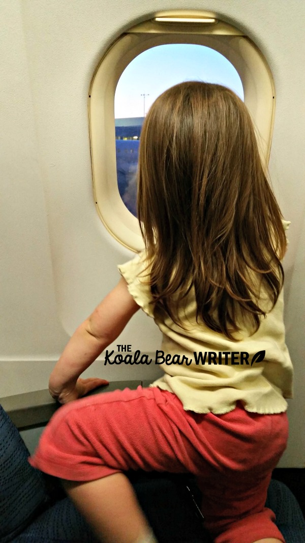 Toddler looking out the window of an airplane.