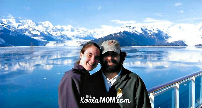 Couple posing in front of a glacier on their Alaska cruise honeymoon.