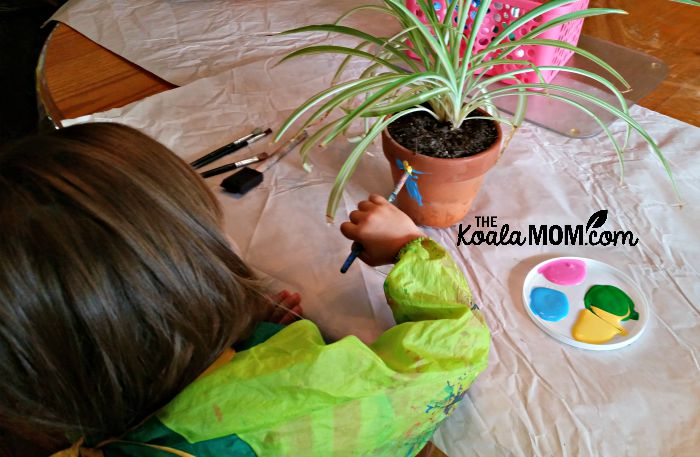 Lily painting her clay plant pot (with spider plant inside)