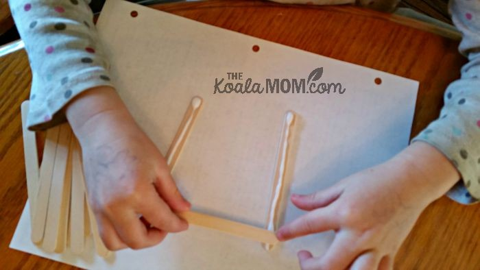 Lily starts gluing her popsicle stick bird feeder
