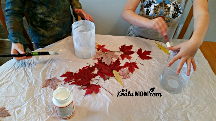 The girls apply Mod Podge and fall leaves to their vases