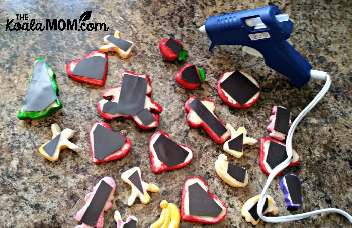 Gluing magnets to the back of salt dough figures with a hot glue gun