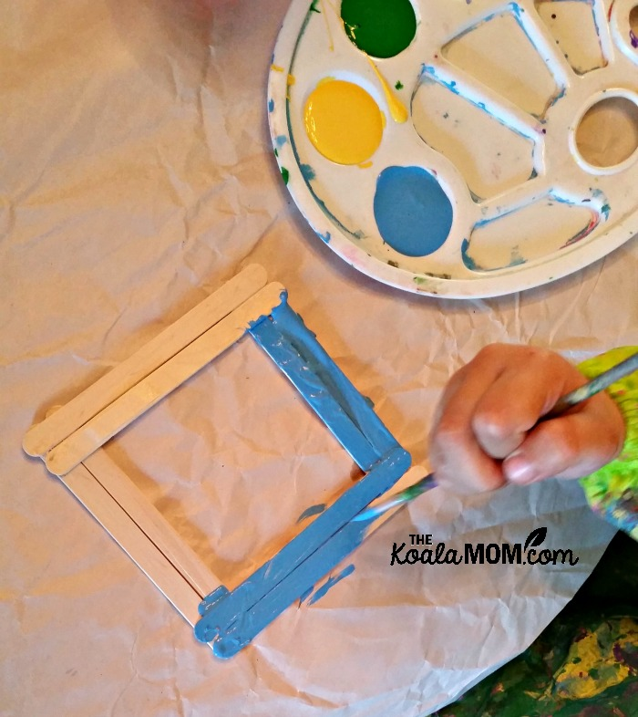 Toddler painting a craft stick picture frame