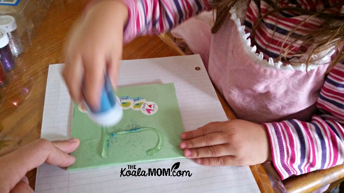 Toddler putting glitter on her notebook cover
