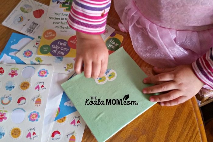 Toddler putting stickers on her notebook cover