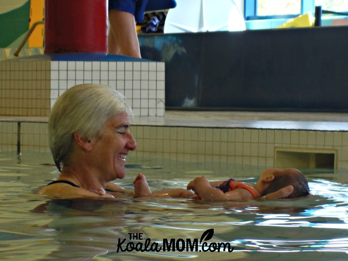 Woman holding baby at swimming pool
