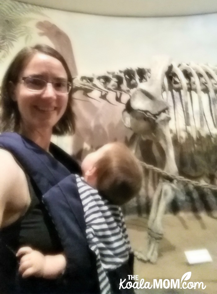 Baby-wearing mom with dinosaur skeleton at the Royal Tyrell Museum