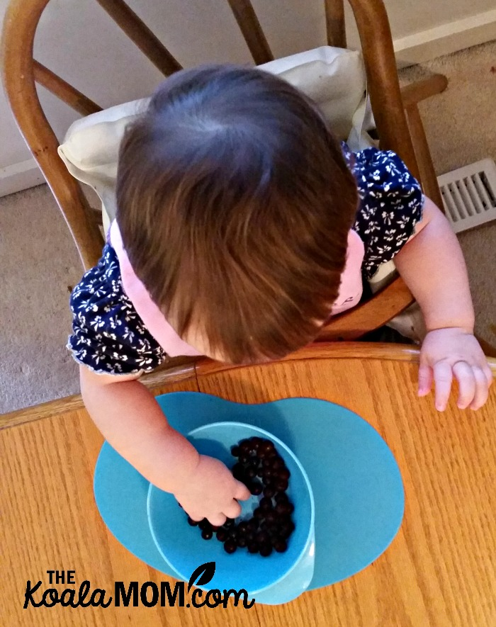 Baby feeding herself with Tommee Tippee's baby mealtime products