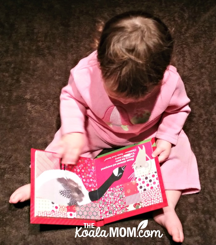 Baby girl reading a Christmas board book