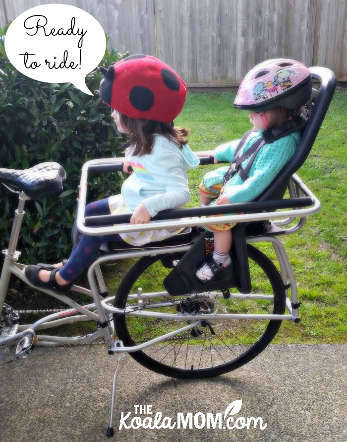 Toddler and a baby on the back of a cargo bike, ready to ride!