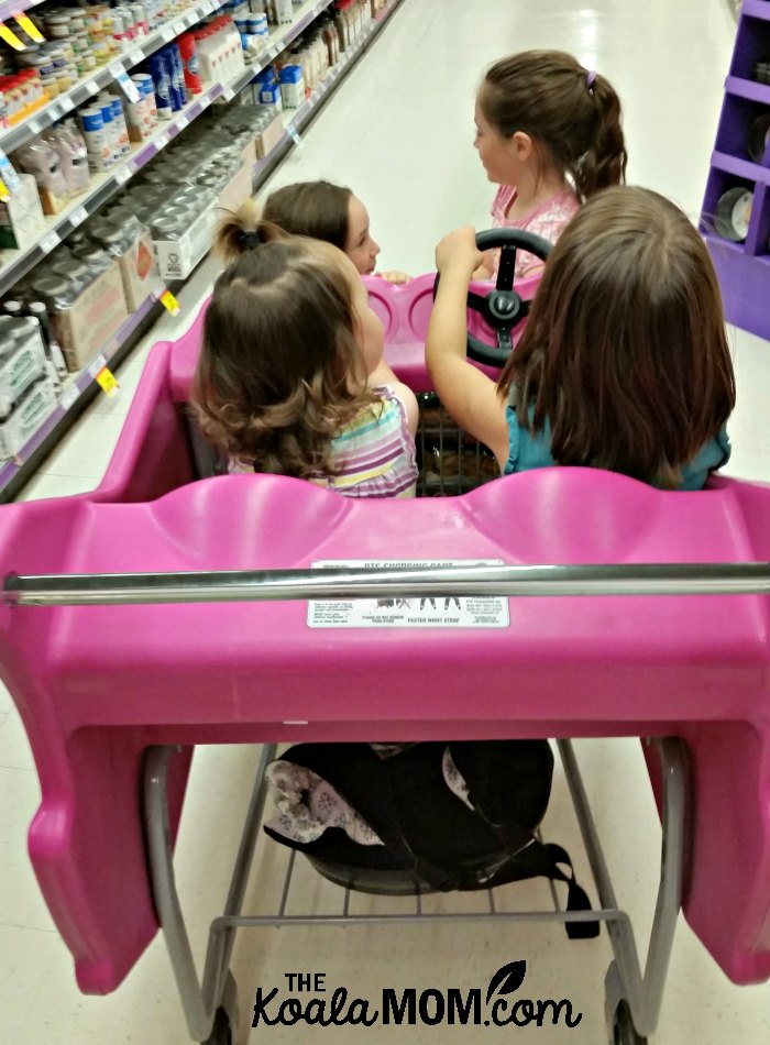 Four kids in a grocery store buggy.