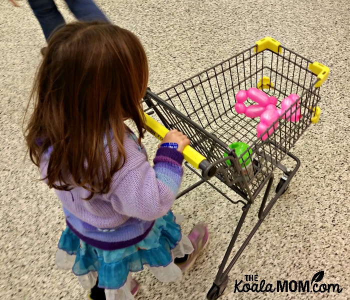 Toddler pushing a child-sized buggy at the grocery store