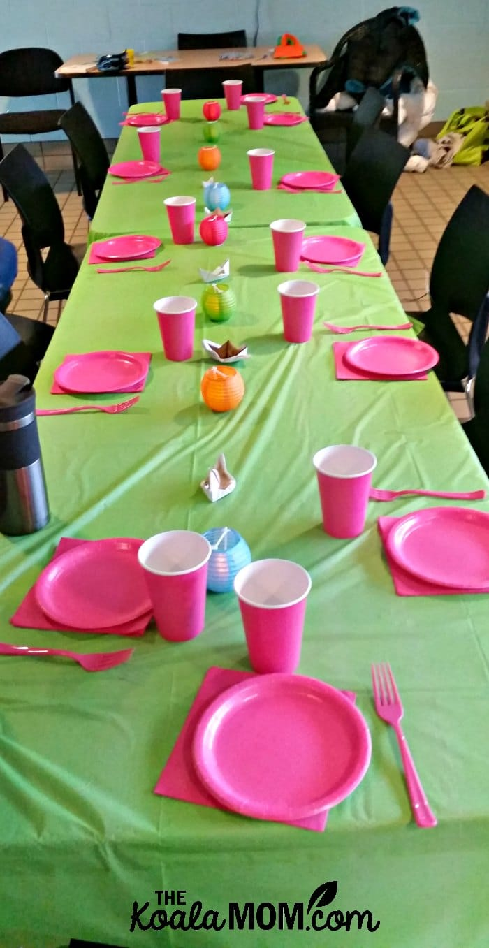 Green and pink birthday party table at a local recreation centre for a pool party.