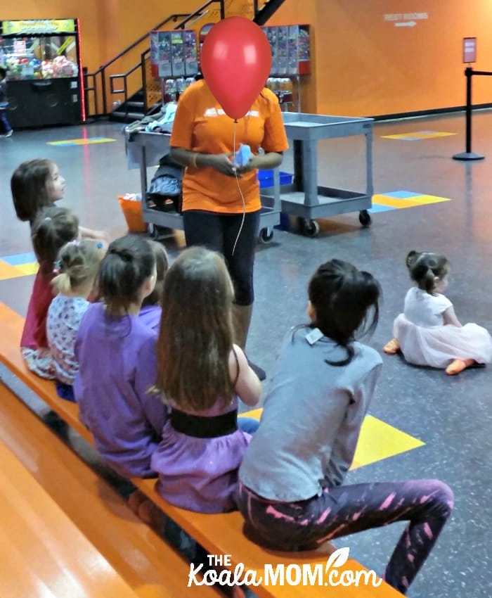 SkyZone staff member explains bouncing rules to a birthday party group.