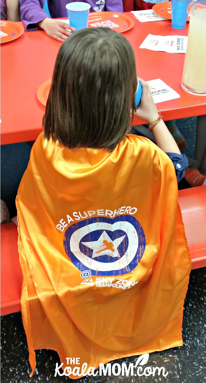 "Jade wearing her ""Be a Superhero"" orange SkyZone cape at her birthday party."