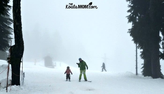 Four-year-old with her ski instructor, returning from a downhill skiing lesson.