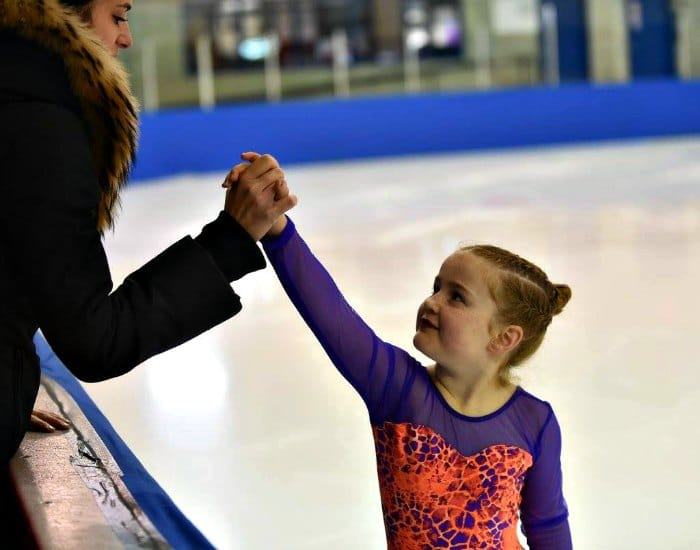 Six-year-old girl doing figure skating and giving her mom a high-five