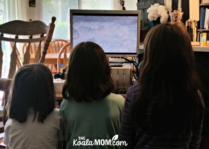 Three homeschool students viewing a video in a media enhanced book