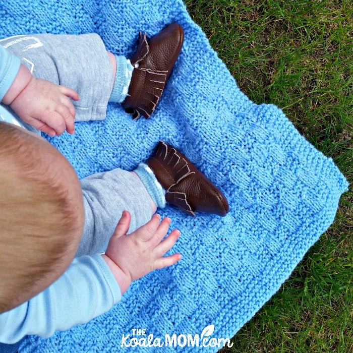 Baby sitting on a blanket wearing his brown fringed moccasins from Mia's Moccs
