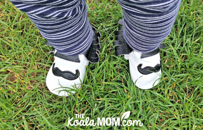 White baby moccasins with black mustaches on them; baby in blue-and-white pants standing on grass