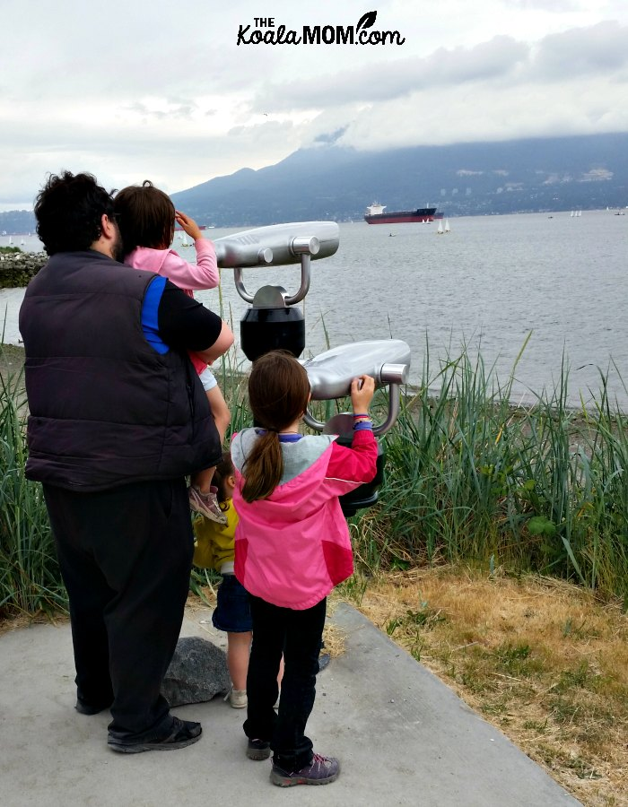 Daddy and daughters peer through binoculars to the ocean at Jericho Beach.