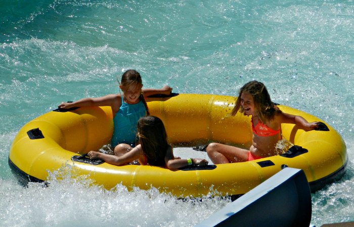 Girls riding a raft down Colossal Canyon at Cultus Lake Waterpark.