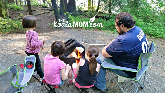 Daddy and daughters making s'mores over a fire at Cultus Lake Campground.