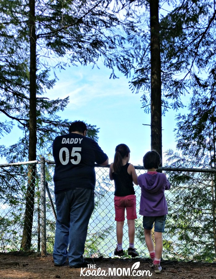 Daddy and two daughters standing at the Teapot Hill Trail lookout.
