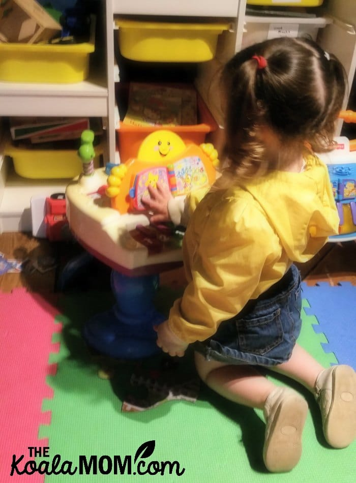 Toddler playing a toy piano in the kids' play area at the Blenheim Pub in the Kitsilano neighbourhood in Vancouver, BC.