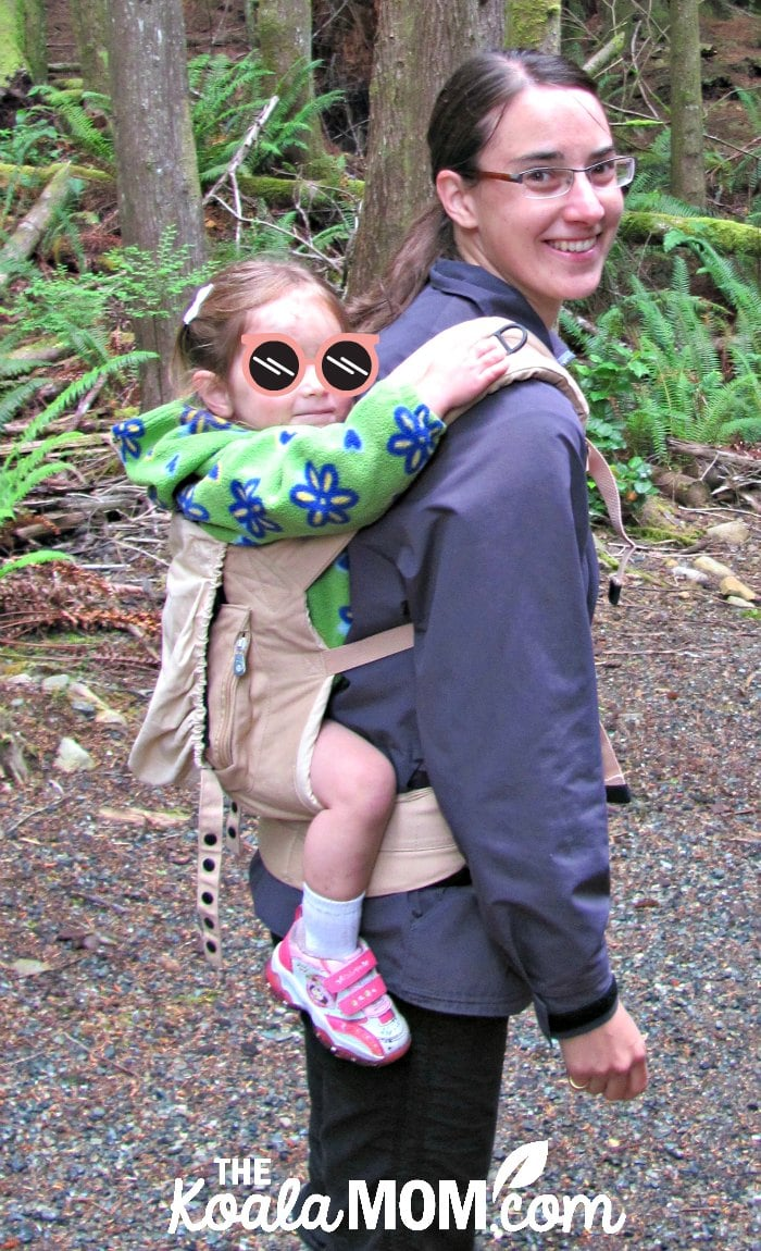 Mom carrying her toddler in an ErgoBaby original carrier.