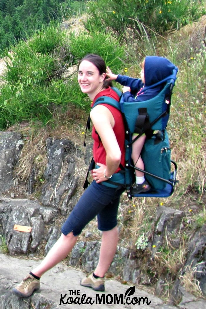 Mom carrying her toddler in a frame baby carrier.