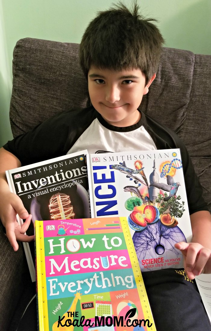 Boy holding three DK books - How to Measure Everything, Inventions: a Visual and Encyclopedia, and Science!