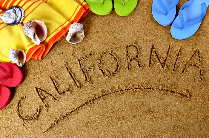 Beach background with towel and flip flops and the word California written in sand (studio shot - directional light and warm color are intentional).